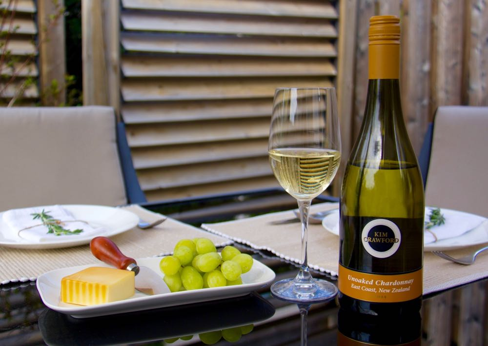 A Bottle Of Kim Crawford Unoaked Chardonnay Next To A Poured Glass Of Kim Crawford Unoaked Chardonnay